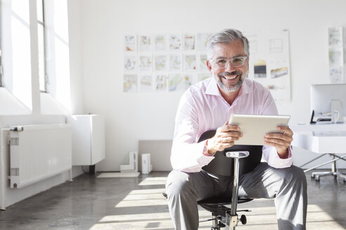 Portrait of smiling businessman with digital tablet in an office - RBF001894