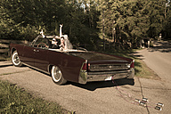Bridal couple sitting in vintage car convertible showing victory-sign - FCF000444