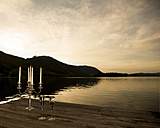 Germany, Bavaria, candle holder and two champagne glasses on a jetty at Schliersee by evening twilight - FCF000446