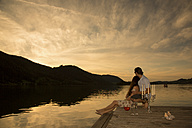 Germany, Bavaria, couple watching sunset from a jetty at Schliersee by evening twilight - FCF000447