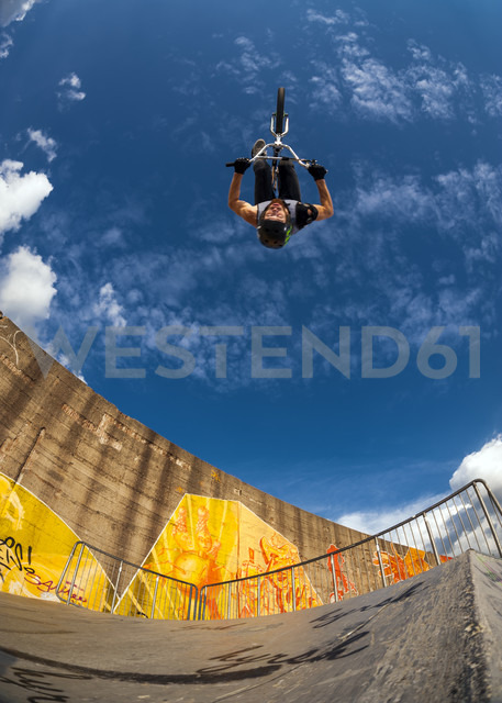 Germany, Young man performing stunt on BMX bike - KJ000308