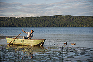 Germany, Rhineland-Palatinate, Laach Lake, Man sitting in a rowing boat and taking a selfie - PAF000904