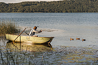 Germany, Rhineland-Palatinate, Laach Lake, Man sitting in a rowing boat and taking a photo of ducks - PAF000905