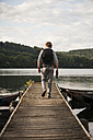 Germany, Rhineland-Palatinate, Laach Lake, Man walking on wooden boardwalk - PAF000909
