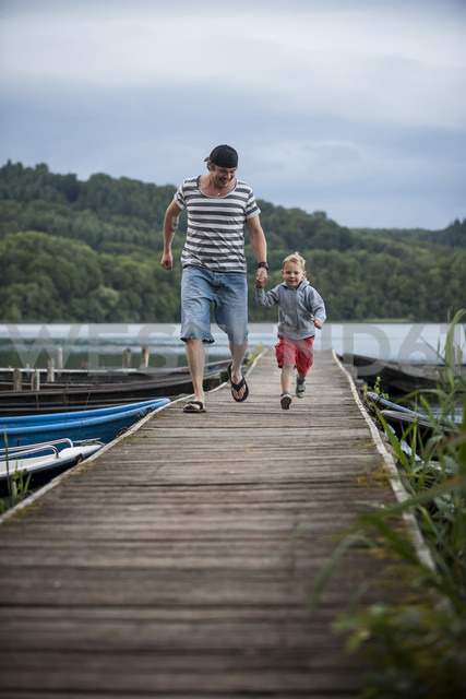 Germany, Rhineland-Palatinate, Laacher See, father running with son on jetty - PAF000925
