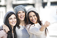 Three female friends with wool caps taking a selfie with digital tablet - ZEF000799