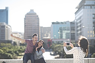 Woman photographing happy young couple with smartphone - ZEF000806