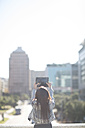 Young woman taking a photo with digital tablet, back view - ZEF000815