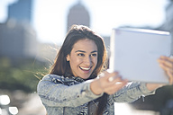 Portrait of happy young woman taking a selfie with digital tablet - ZEF000818