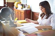 Teacher writing at desk - ZEF000707