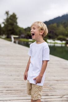 Laughing little boy standing on a jetty - DAWF000108