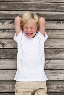 Portrait of laughing little boy lying on a jetty - DAWF000111
