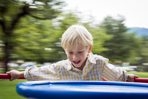 Portrait of smiling little boy standing on a carousel of a playground - DAWF000147