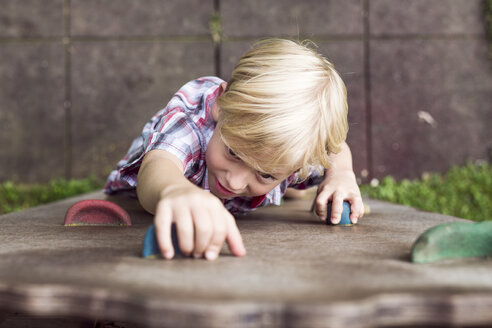 Portrait of little boy climbing on a playground - DAWF000136
