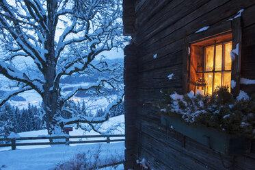 Austria, Salzburg State, Altenmarkt-Zauchensee, facade of wooden cabin with lightened window in winter - HHF004865