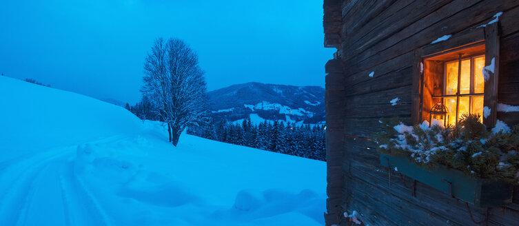 Austria, Salzburg State, Altenmarkt-Zauchensee, facade of wooden cabin with lightened window in winter - HHF004861