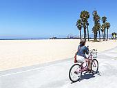 USA, California, Santa Monica, woman on bike near the beach - JLR000004