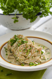 Slices of selfmade napkin dumplings with champignon sauce and parsley - ODF000810