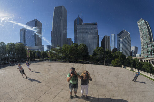 USA, Illinois, Chicago, reflection of two photographers standing in front of Cloud Gate on AT and T Plaza taking a picture - FO006982