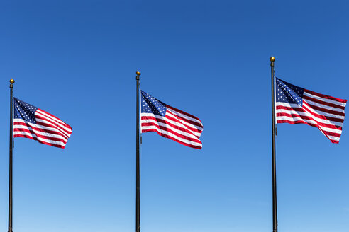 Three American flags against blue sky - FOF007136