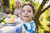 Boy eating pasta with grandmother sitting at garden table - MFF001246