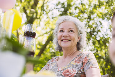 Smiling senior woman holding glass of red wine in garden - MFF001253