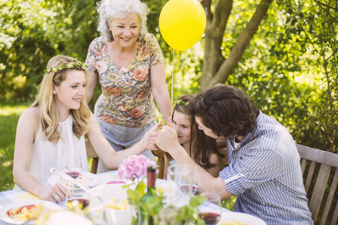 Family of three generations congratulating girl on a garden party - MFF001256