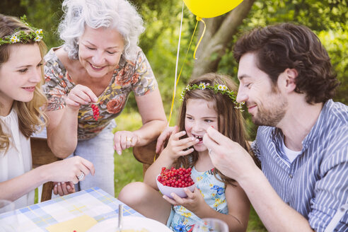 Family enjoying a bowl with redcurrants at table outside - MFF001265