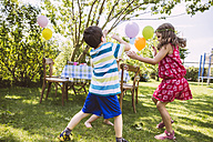 Children trying to catch soap bubbles in garden - MFF001274