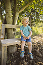 Smiling boy sitting on bench under tree - MFF001279