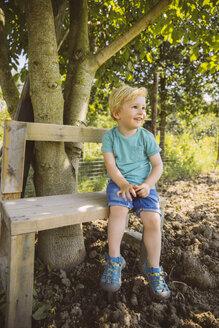 Smiling boy sitting on bench under tree - MFF001279