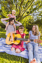 Family on picnic blanket playing guitar - MFF001306