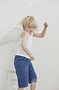Portrait of smiling little boy wearing angle wings posing on a chair - MJF001349