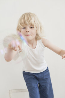 Portrait of smiling little boy watching a soap bubble - MJF001338