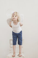Portrait of little boy with angle wings watching a soap bubble - MJF001345