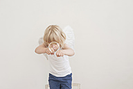 Portrait of little boy with angle wings fighting against a soap bubble - MJF001347