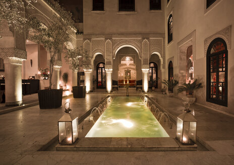 Morocco, Fes, Hotel Riad Fes, courtyard with lightened pool by night - KMF001464