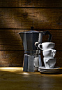 Espresso can and stack of three espresso cups in front of wooden wall - KSWF001331