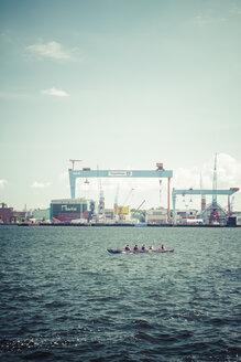 Germany, Schleswig-Holstein, Kiel, Harbour, Rowing boat in front the dockyard - KRP001069