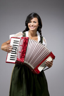 Portrait of smiling young woman with accordion wearing dirndl - MAEF009041