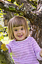 Portrait of smiling little girl sitting on an apple tree - LVF001779