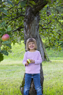 Portrait of little girl leaning on an apple tree - LVF001797