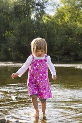 Little girl walking in water at riverside - LVF001804