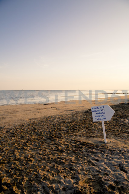Italy, Gorizia, Grado, view to sandy beach with direction sign at evening twilight - LVF001805