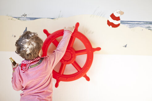 Toddler playing with red wheel fixed on a wall - AFF000083