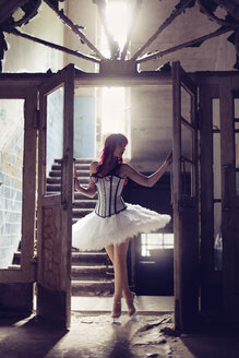 Germany, Brandenburg, Beelitz, woman with red hair and ballerina dress standing in destroyed old house at backlight - AFF000149