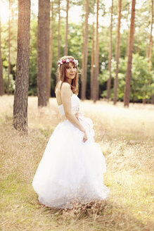 Bride wearing white wedding dress and flowers walking on a meadow - AFF000076