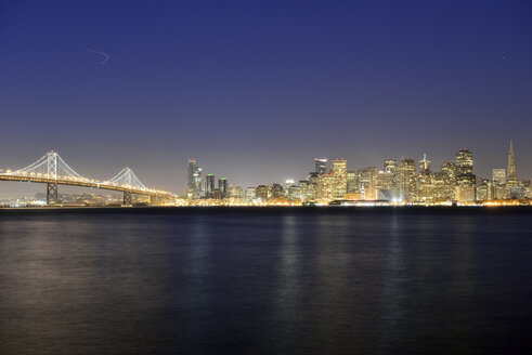 USA, California, San Francisco, Oakland Bay Bridge and skyline of Financial District at night - BRF000780