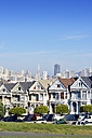 USA, California, San Francisco, Victorian houses at Alamo Square in front of the skyline - BRF000693