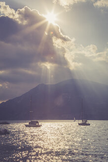 Italy, Veneto, Brenzone, Sailing boats on Lake Garda against the sun - LVF001818